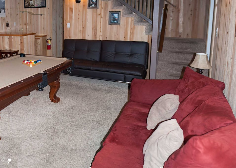 Very comfortable sleeper futon in game room along with couch and love seat