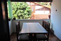 Varanda do segundo andar com mesa com 6 cadeiras.