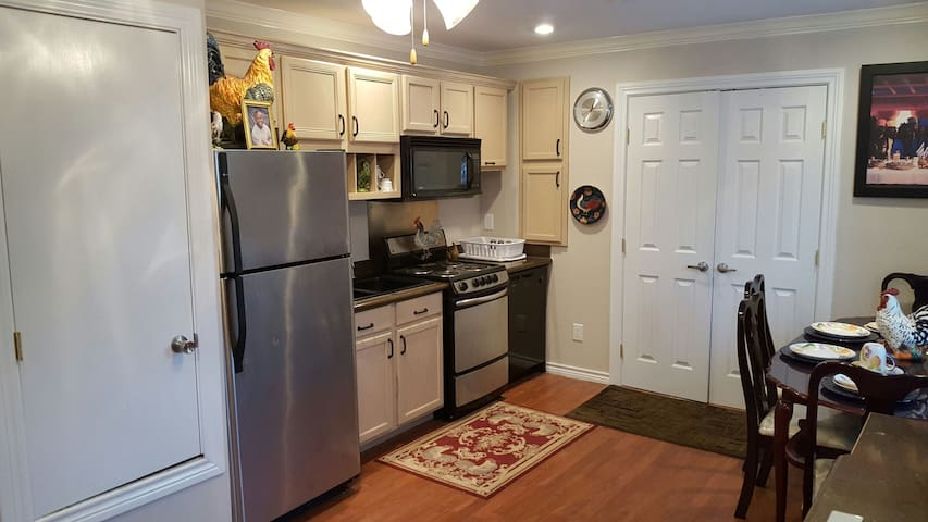 Kitchen sink, full stove, microwave, refrigerator and freezer, dining table, double door entry into restroom