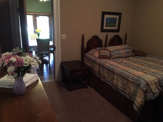 AirBNB guest bedroom with queen bed, side table, chest of drawers.