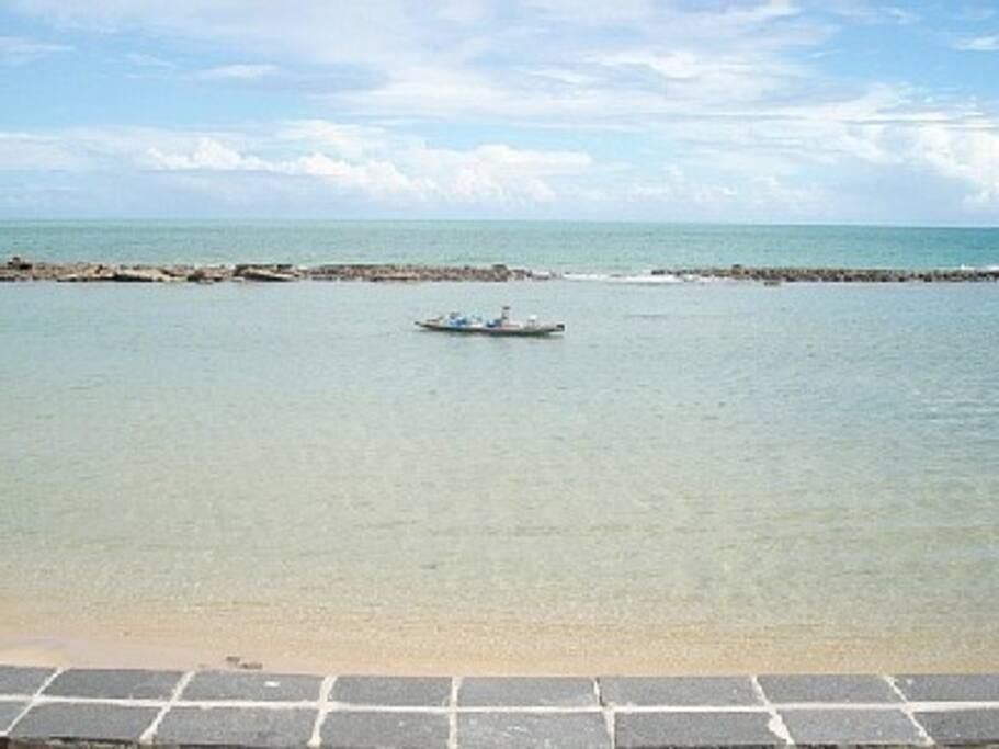 Vista do mar tranquilo, de águas rasas e quentes. Ideal para crianças.