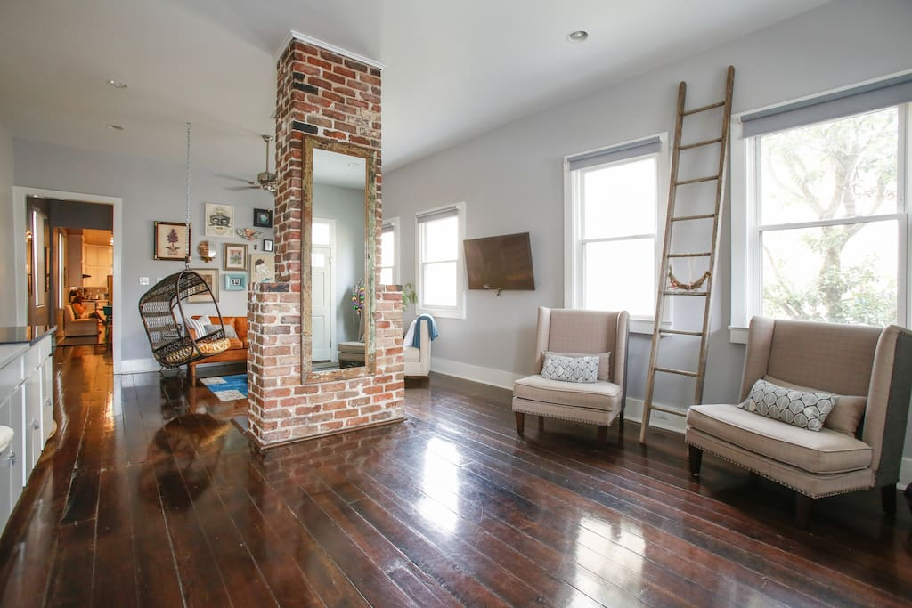 Bright and airy floorplan in the living room, with an exposed brick fireplace that is original to the house.