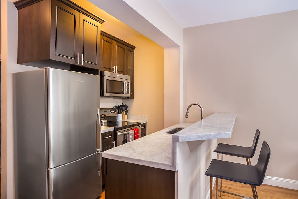 Fully equipped kitchen with marble counter-tops, gas range stove and cooking utensils