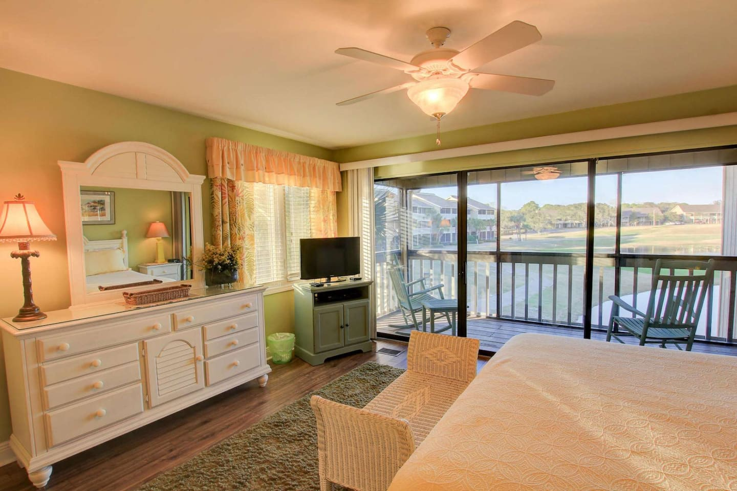 Master bedroom with king size bed, private access to waterfront patio, flat screen TV, ceiling fan, triple dresser