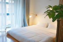 特意打造的地台,打掃絕不將就,是能光著腳感受到的乾淨,大床依靠的是向南的落地大玻璃,暖暖的陽光溢進房間
