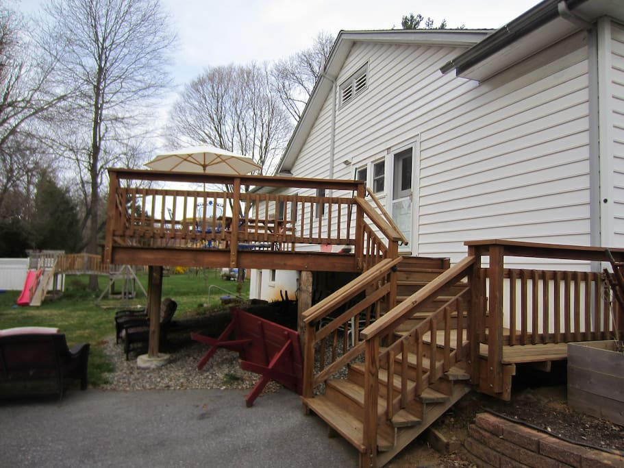 Private 16 ft. x 24 ft. deck, overlooking backyard with large playset and trampoline