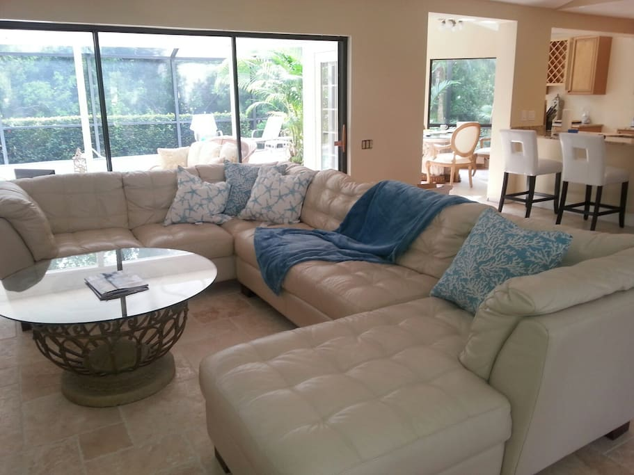 Great room features extra large leather sectional, wall of sliders to lanai, and cathedral ceiling.