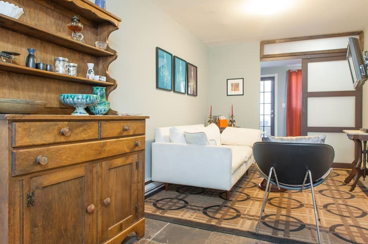 Eclectic open living room with couch that can fit an extra guest (not a sleeper sofa).