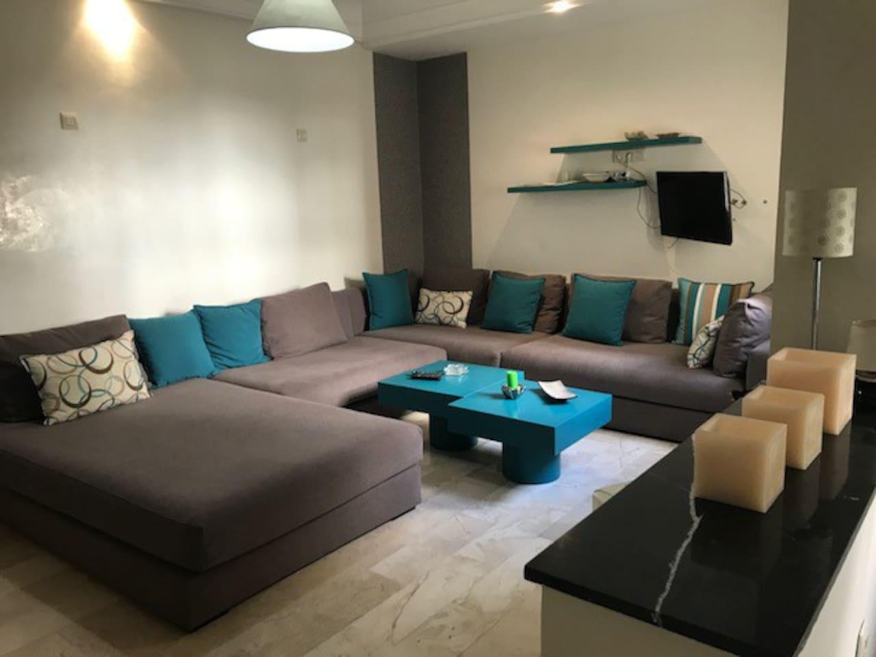 """Grand salon en angle complété par un bed, très convivial, décoré avec beaucoup d'attention, la partie """"bed"""" sera un parfait lit d'appoint. Le salon peu recevoir jusqu'a 8 personnes."""