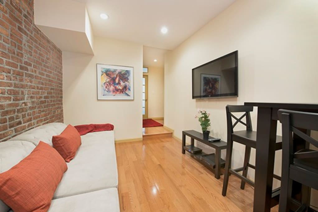 Gorgeous Exposed Brick Accents in our newly renovated Living room. Custom Tillary Couch which turns into a twin bed. Utmost comfort and Utility. The large Bar table has 4 chairs lets everyone gather together.
