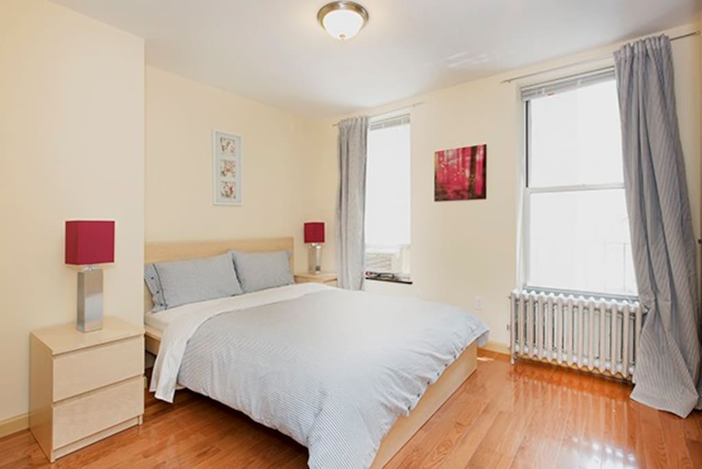 The Second Bedroom which is large and accommodating. New hardwood floors and large closet space. Custom Lamps with Elegant lighting and Sleek Red Nightstands. Large plush Queen Bed and two large windows. Air conditioner in each bedroom.