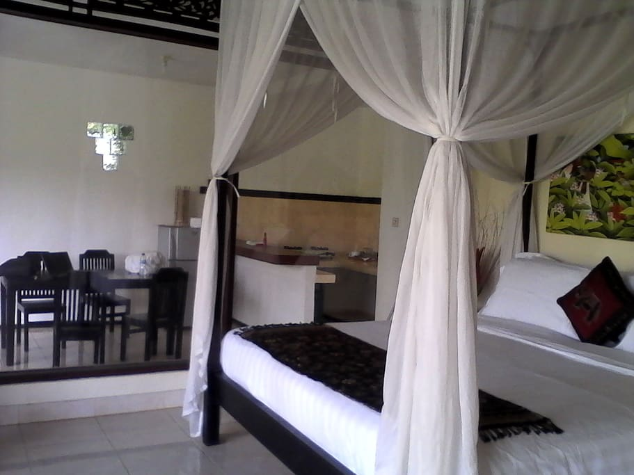 king size bed with romantic sheet, duvet and mosquito net