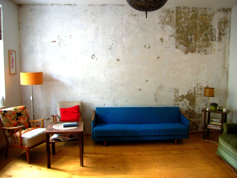 out of date living room shot, showing the exposed concrete wall and sofa.  All other photos are current!