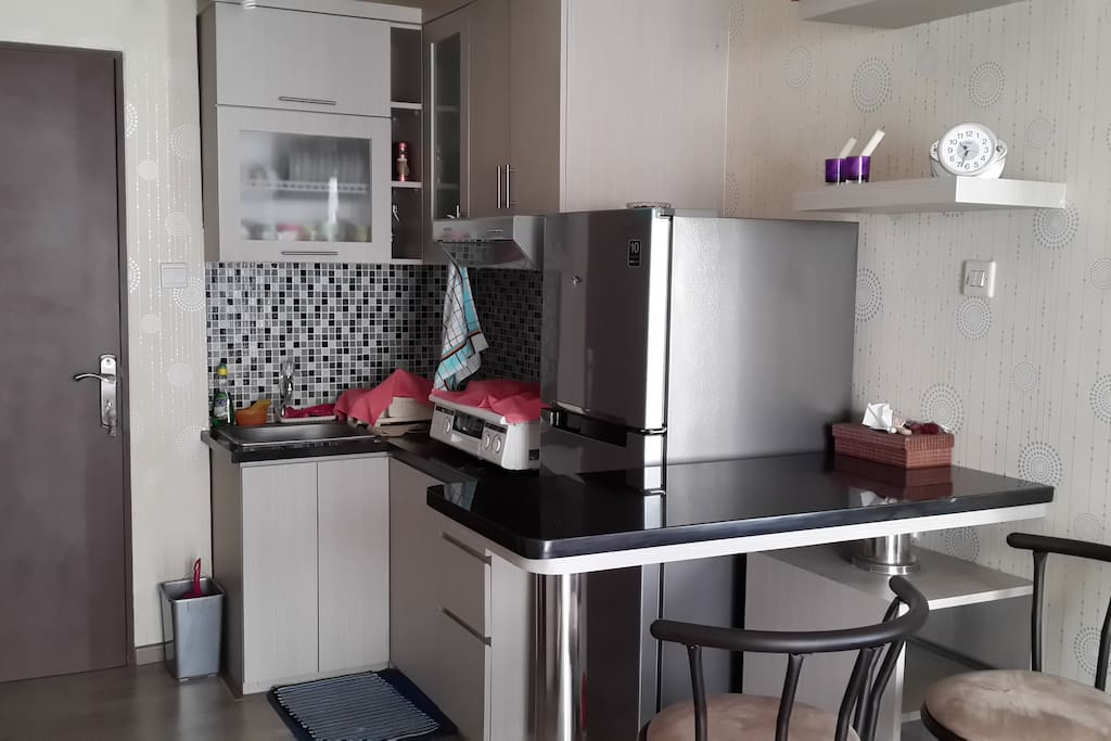 Small kitchen and fridge, also with complete plates and cutleries.