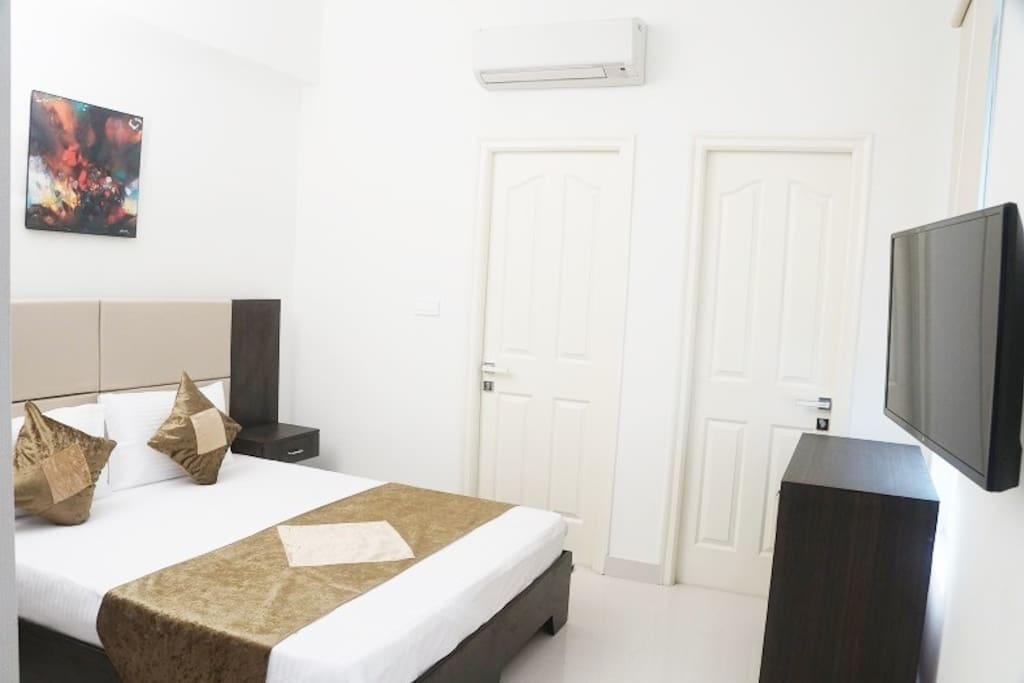 Bedroom with attached Bathroom, Work Desk & Flat screen TV showing Tata Sky HD with international channels