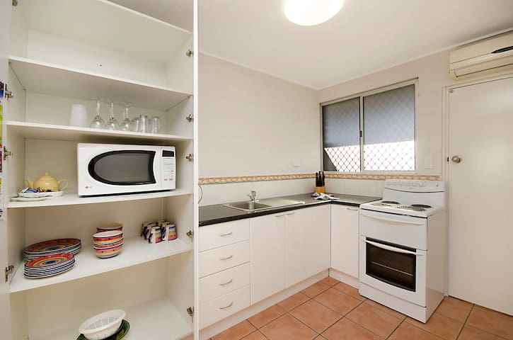 Fully equipped kitchen with full-sized stove, large fridge, microwave, crockery and cutlery.