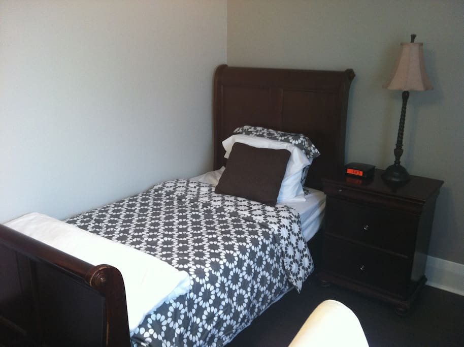 Back bedroom with comfy foam mattress sleigh bed with graphic  linens