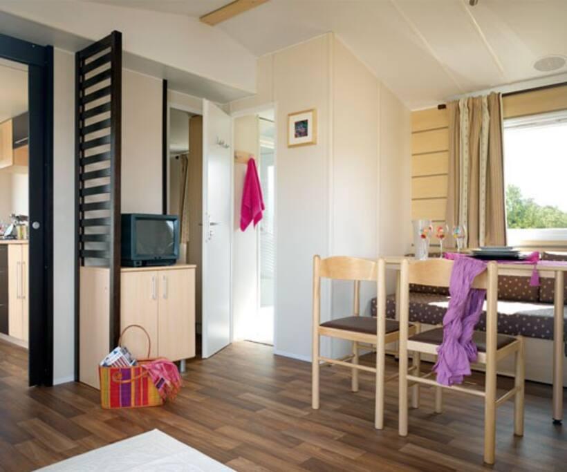 Agréable salon ouvert sur la terrasse avec une banquette convertible pour un lit à 2 places
