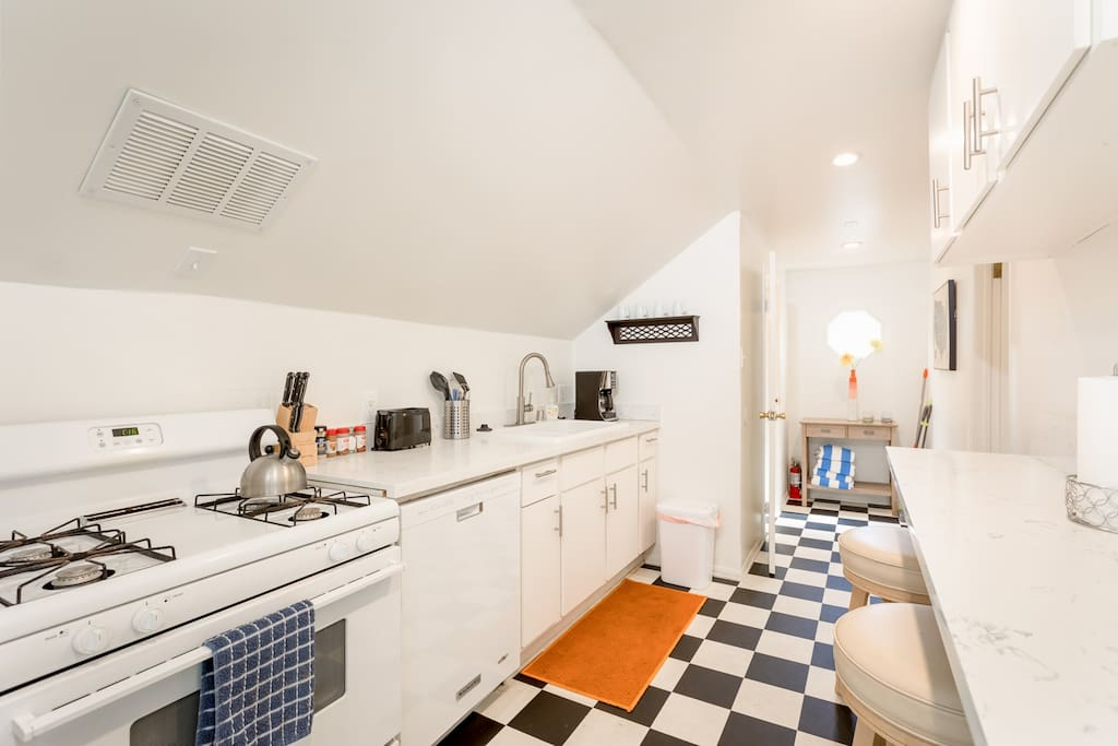 Charming kitchen with gas stove, dual sink, and counter seating for 3.