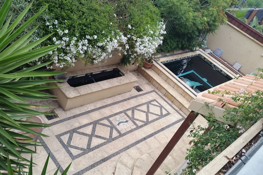The view of the beautiful landscaped patio area with water feature and spa.