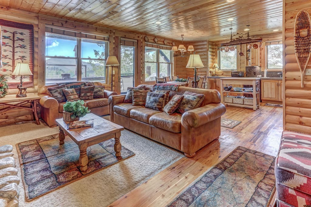 Log Cabin Design Condo with Great Room featuring a Living Room with a Stone Fireplace, Fully Equipped Kitchen, Dining Area, Hardwood Floors, and Private Deck