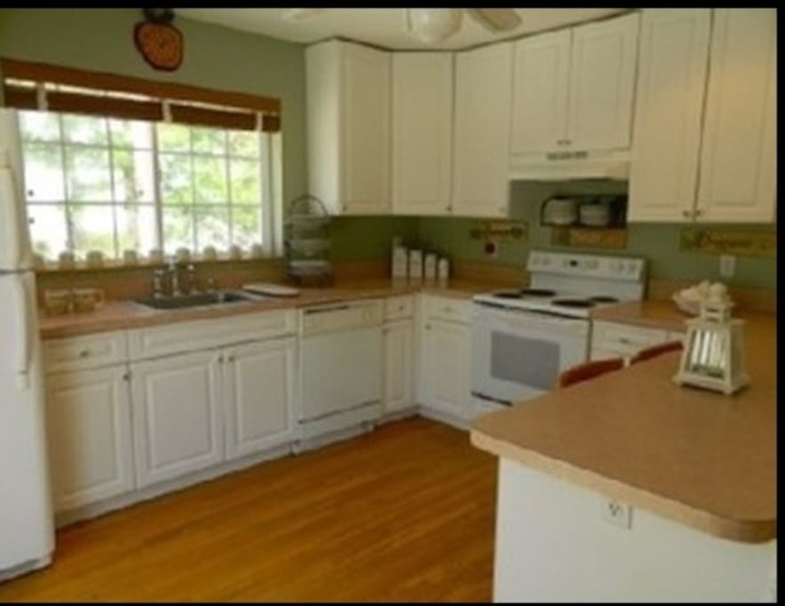 Open bright airy kitchen with an island that seats 4-5ppl