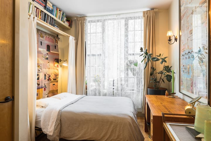 This cozy bedroom gets excellent light and is tastefully decorated. The crafts give it a chill Southwest vibe, the desk is MidCentury, and some elements are bric-a-brac.