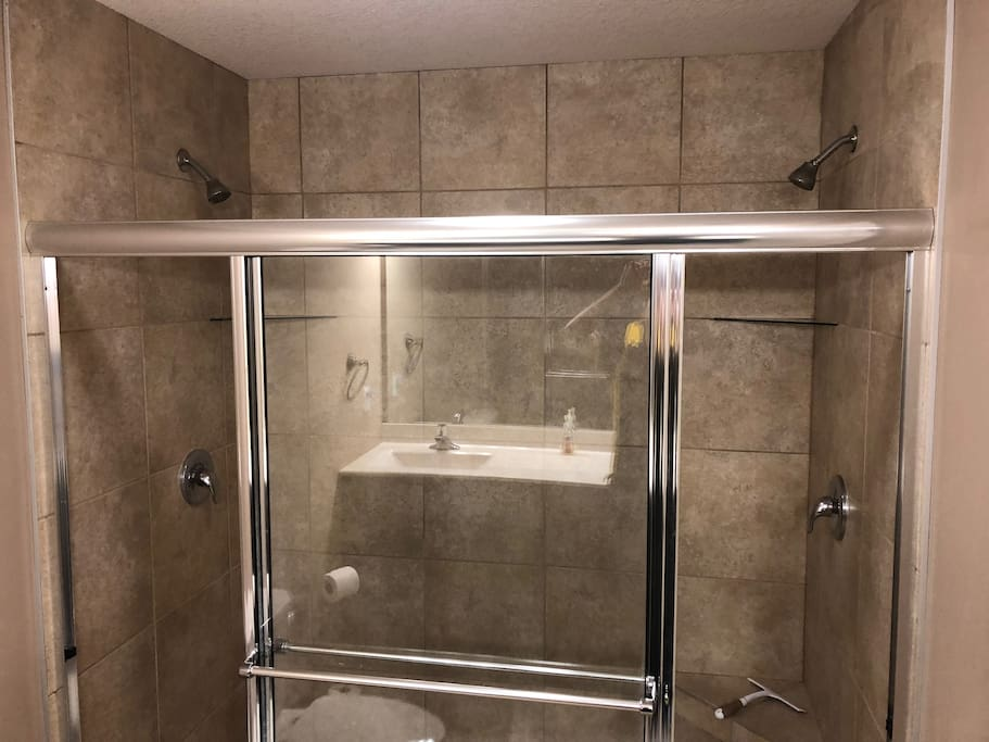 Private Custom Tiled Double Headed Shower and Double Vanity Sink in Reflection.
