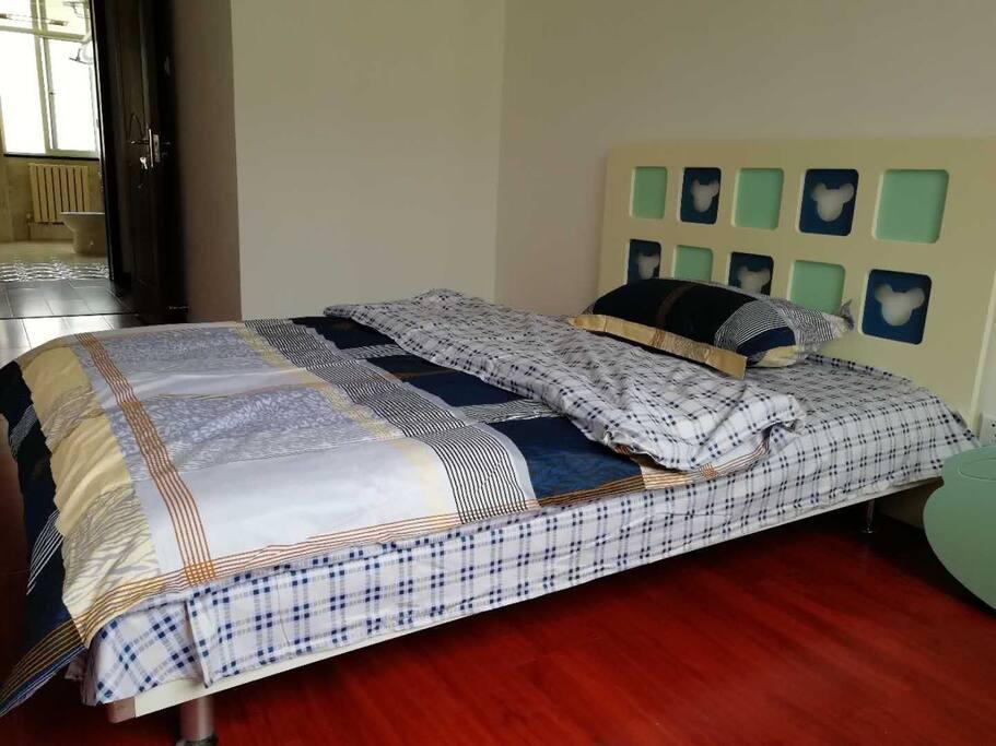 这是卧室2,配有一个一米五的米奇双人床和一个床头柜和衣架