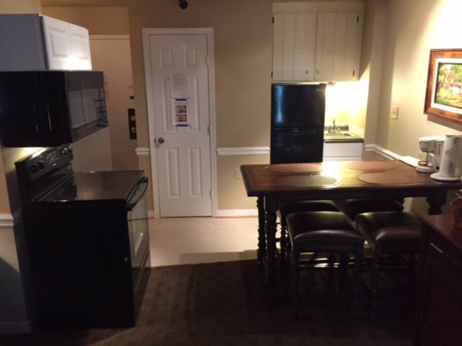 Small kitchen area includes a full-sized range and microwave, a 10 cubic foot fridge/freezer, a small sink, and many small appliances as well as posts, pans, utensils. and