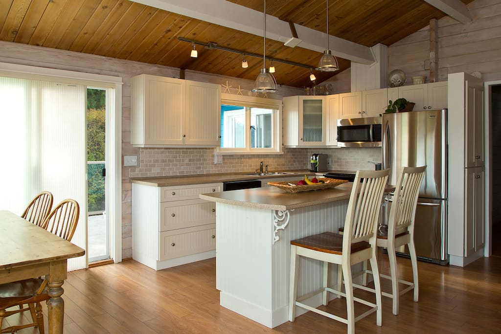 Open kitchen with island seating area and at a farmhouse table overlooking the ocean.