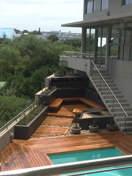 Seating area next to pool with open fire pit / braai