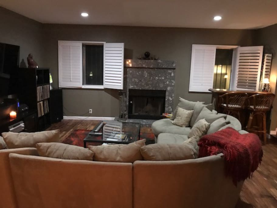 "Living Room with 75"" Flat Screen TV, fireplace and bar"