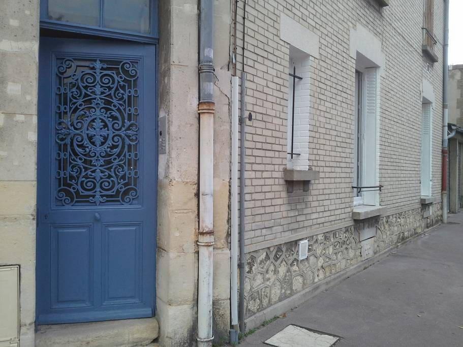 Entrée de l'immeuble et les trois fenêtres de l'appartement