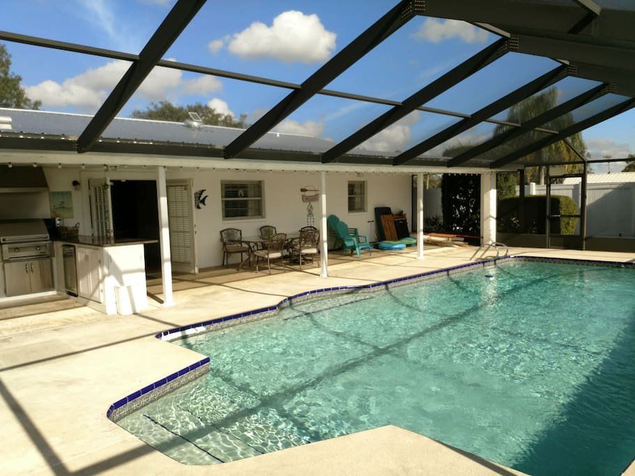 Pool, summer kitchen, Veranda and blue sky through screened in pool area