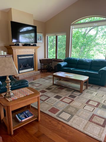 """Living room overlooking the lake, with a cozy gas fireplace and 60"""" Smart TV."""
