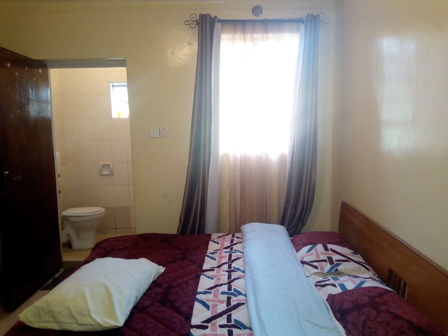 Self contained bedroom with closets and double bed.