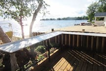 The L-shape Deck Table is big enough for 50 people to eat while enjoying the Canada geese, Families of Baby Ducks, and early in the morning to share with the deer which come up to the Deck Steps and the variety of birds including hUMMINGBIRDS,  etc.