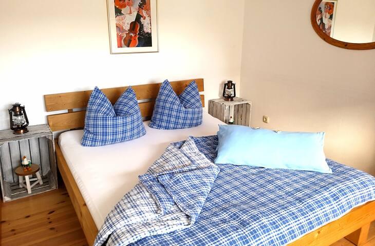 Ein Schlafzimmer  mit 1,60  Doppelbett, kleinem Tisch, 2 Korbsesseln und Kleiderschrank
