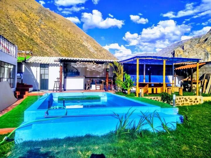 Casa de Campo frente a montañas y río.