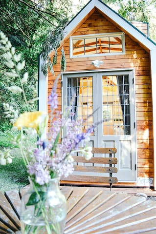 The antique french doors open up to your private yard that expands into the park with at teak table and chairs, daybed and bbq