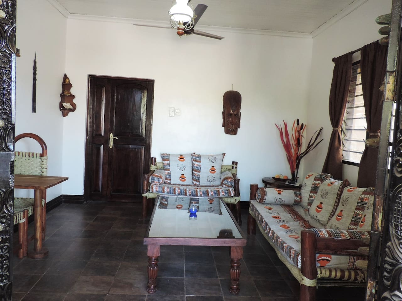 spacious african themed living room,with windows overlooking the gardens in the compound