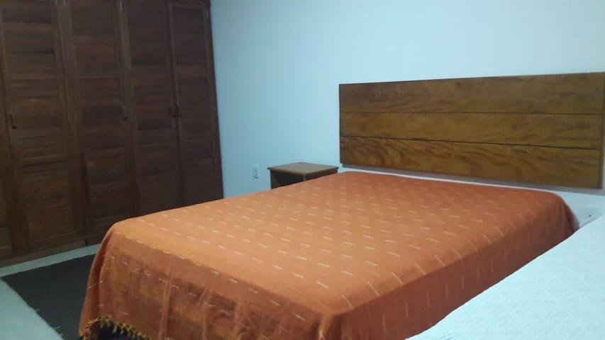 Quarto amplo com cama de casal queen size, cama solteiro e ar condicionado.