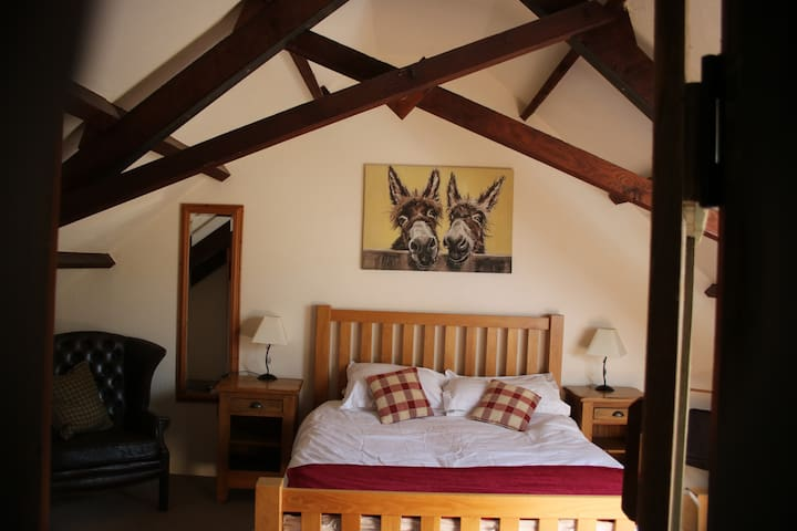A king size bedroom, with a wardrobe, bedside tables, comfy chair, dressing table and towel rowel.   Lovely country views.