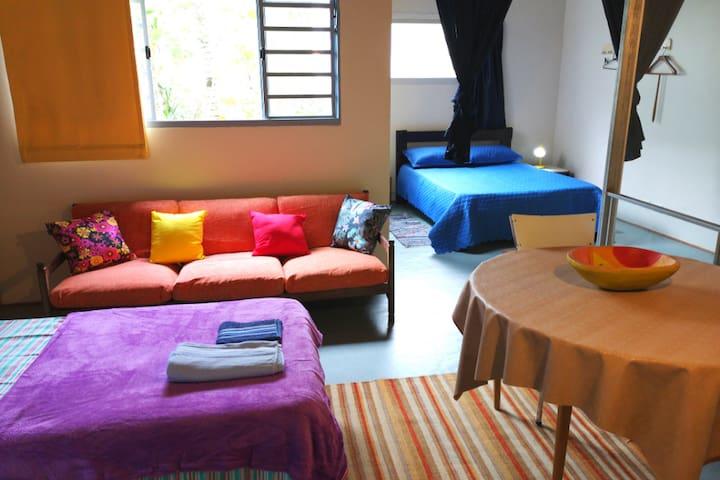 Estúdio no segundo andar da casa com uma cama casal e dois camas solteiros