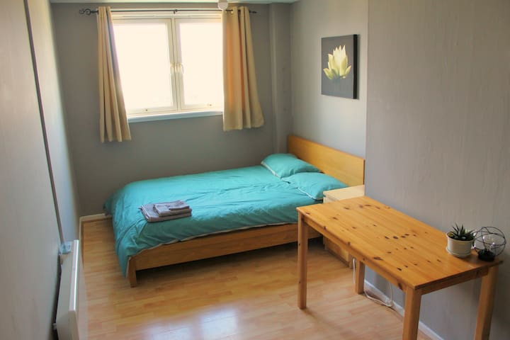 Guest Bedroom featuring a double bed, side table and desk. Ideal for anyone wanting to relax with a laptop or plan their day trips.