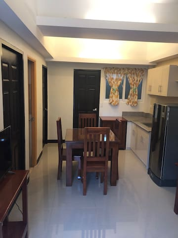 Kitchen area furnished with a refrigerator, kitchen utensils, dining table and chairs.