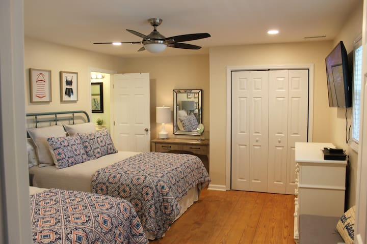 First bedroom with two queen beds. Flatscreen TV, closet, and attached bathroom