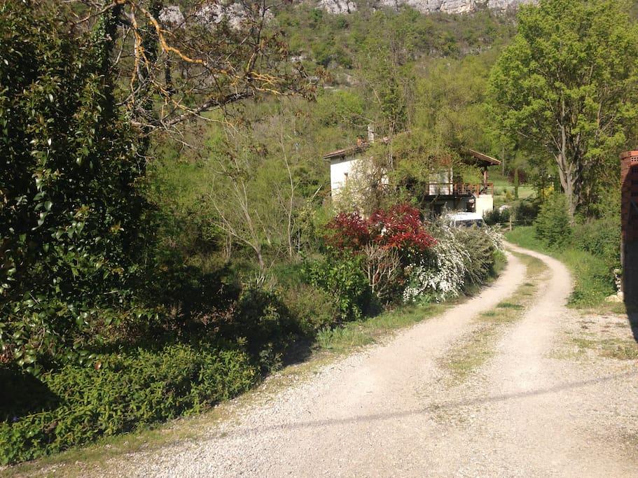 la maison vue du chemin, en retrait, dans son petit coin tranquille.