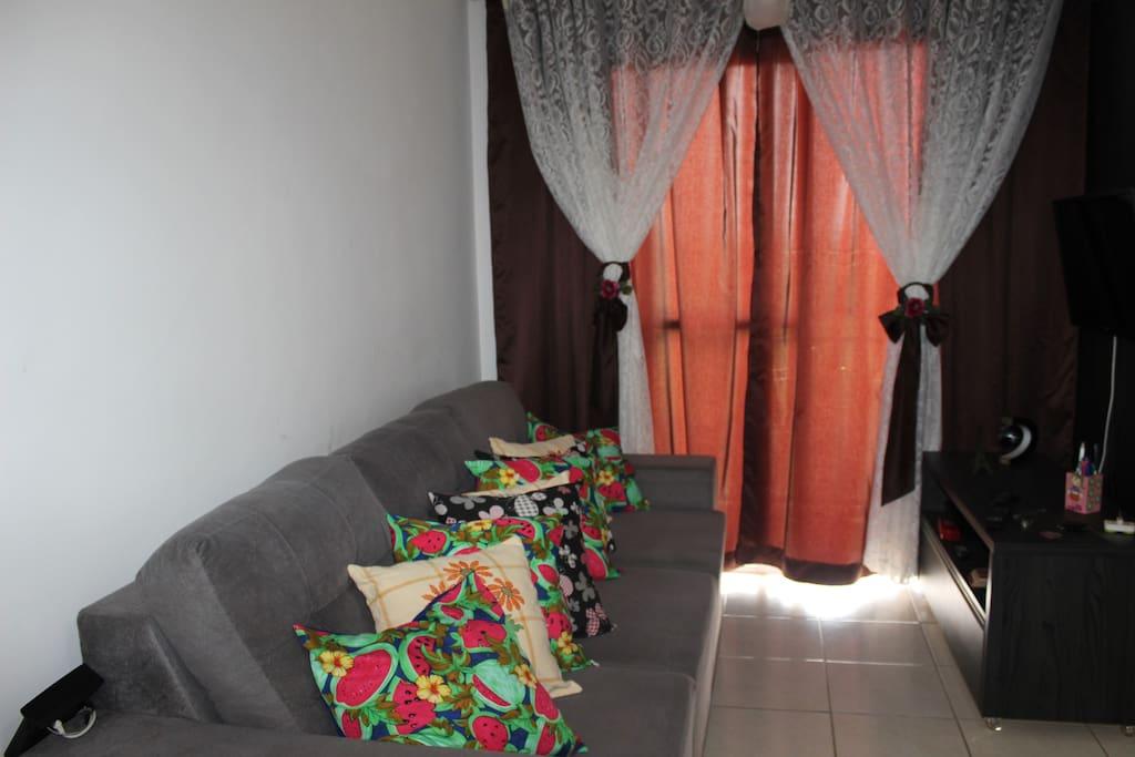 Sala de estar com televisão, sofá-cama retrátil de casal, cortinas, espaço para um colchão de solteiro e mesa de jantar.